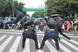 Indonesian university students perform on the street during a road safety campaign in Jakarta