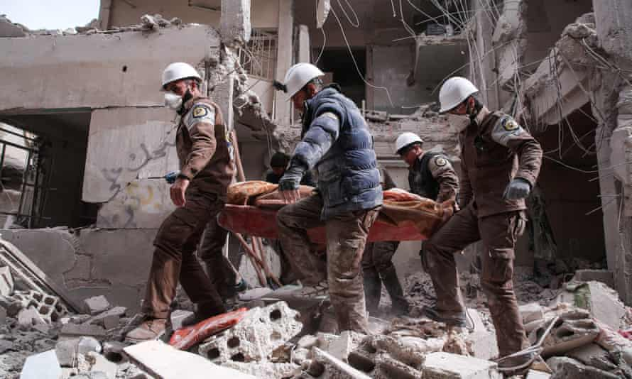 Members of the White Helmets search for survivors following an airstrike on a rebel-held neighbourhood on the outskirts of Damascus in 2016.