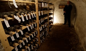 A security guard stands next to shelves with bottles of 19th-century wine in the cellar of Becov castle in Becov nad Teplou, Czech Republic.