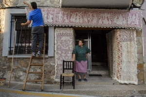 A man celebrates by decorating the entrance to a house with embroidered blankets