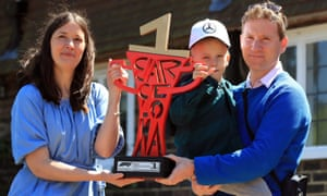Harry Shaw, and his parents James and Charlotte, hold Lewis Hamilton's Formula One trophy from the Spanish Grand Prix.
