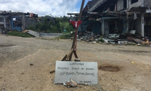 A sign warns of unexploded ordnance inside in Marawi. Military engineers are checking and disposing of them. The military says the job won't be done until October 2018.