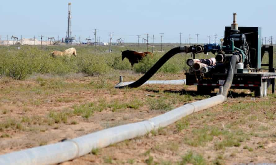 Large hoses lead from one hydraulic fracking drill site to another as horses graze in a Midland, Texas, field.