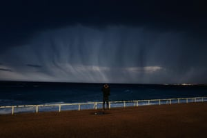 A man looks at a thunderstorm above the Mediterranean sea from the French riviera city of Nice.