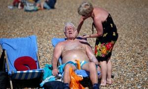 A woman applies sun cream to a man on a beach.