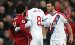 Luka Milivojevic confronts Mohamed Salah of Liverpool after he goes down.