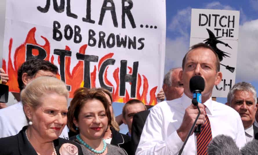 """Tony Abbott speaking at a rally with a banner behind him saying """"JuLiar Bob Browns BITCH'"""
