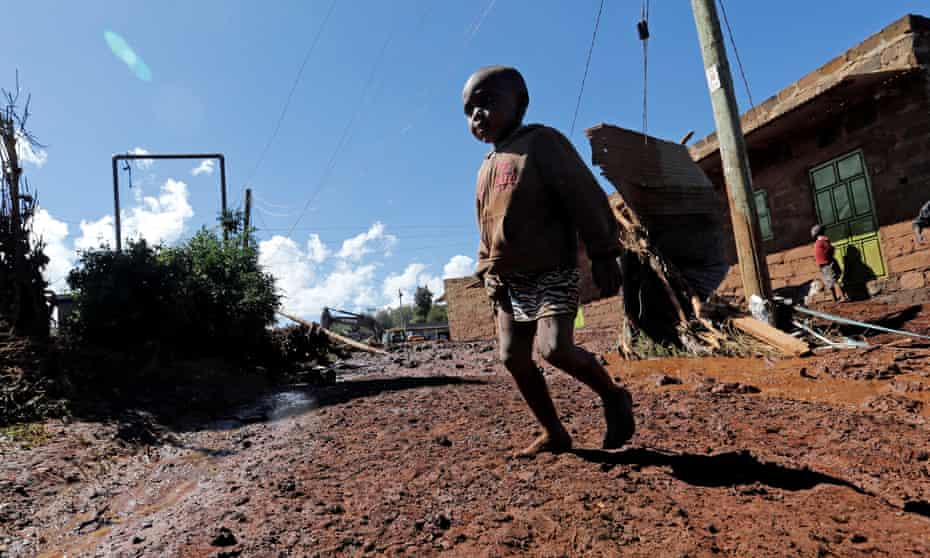 A child walks near houses destroyed by flooding after the Patel dam burst.