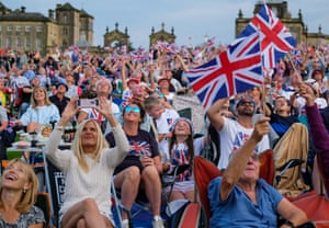 Malton, UK Audience members look to the skies as as a Spitfire aircraft performs a flypast at the start of Yorkshire's biggest open-air proms of the summer at Castle Howard