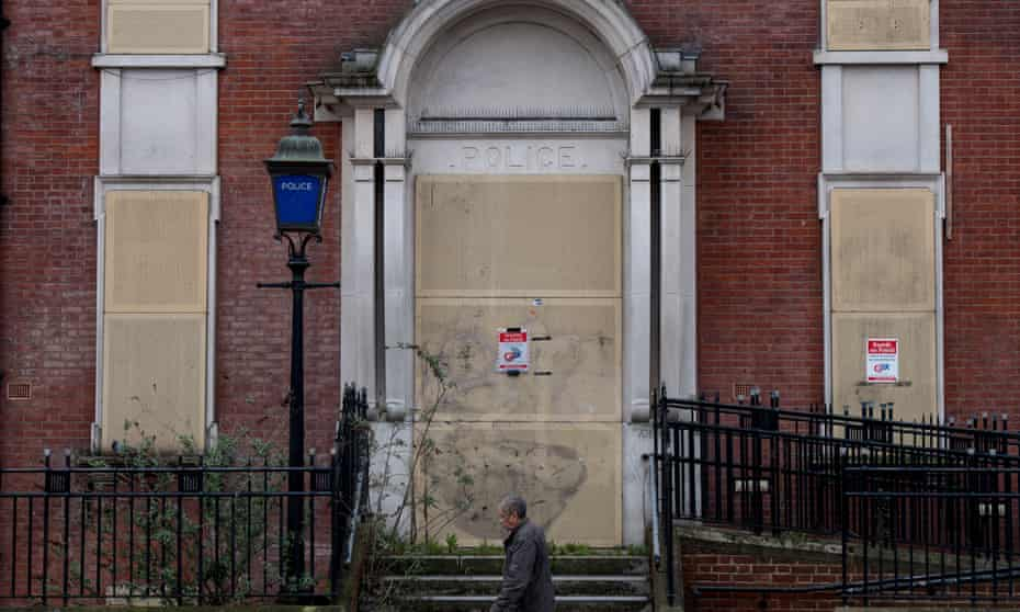 A man walks past a closed and boarded-up police station in Hackney, east London, in 2018