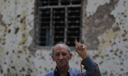 A voter in Mosul shows his ink-stained index finger as proof of having cast his ballot