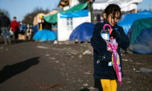 A young girl walks along a muddy road in the makeshift migrant camp in Grande-Synthe near Dunkirk