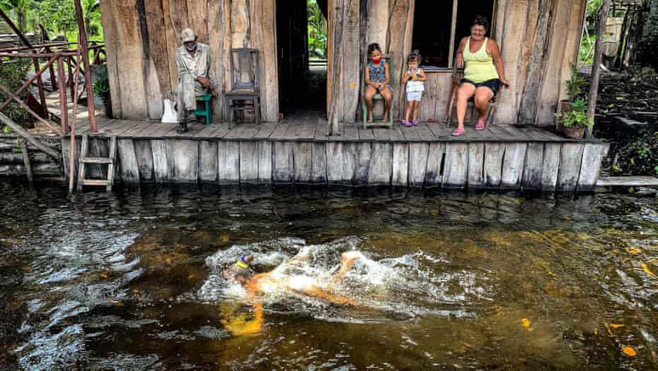 A woman swims near a family of charcoal producers.