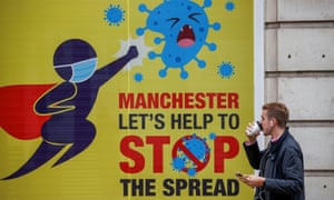 A man walks past a public health poster in Manchester