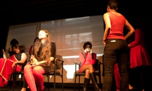 Garima, left, sits with headphones as the cast of Yoni ki Raat (Night of the Vagina) surround her during her performance set in a subway car