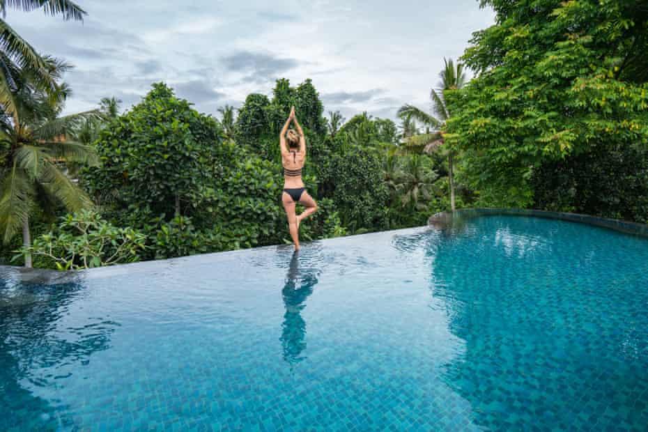 Wanita muda berdiri di tepi infinity pool, Ubud, Bali