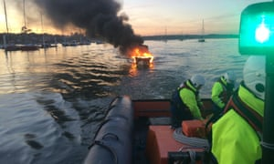 Flames and black smoke on the water with a rescue boat in the foreground