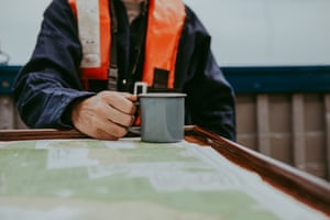 A mug of tea on a table that also holds a map onboard the Salford whelk boat off the north Norfolk coast.