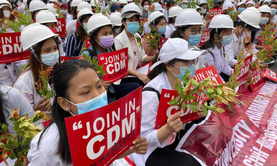 Medical students wearing face masks hold placards as they gather during an anti-coup protest in Mandalay on 21 February.