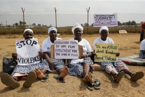 Women hold placards by a roadside in Monrovia, Liberia
