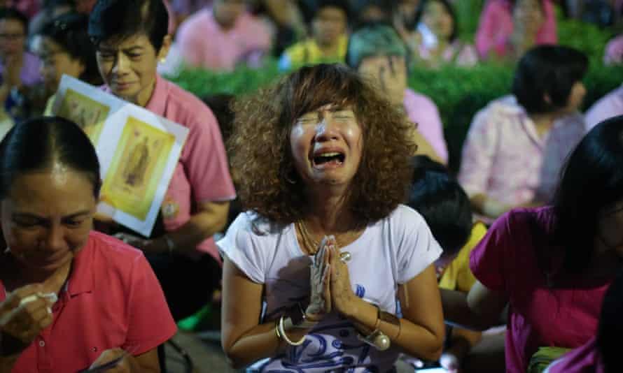 Thai women cry as they hear the news of the death of Thai king Bhumibol Adulyadej outside Siriraj hospital in Bangkok