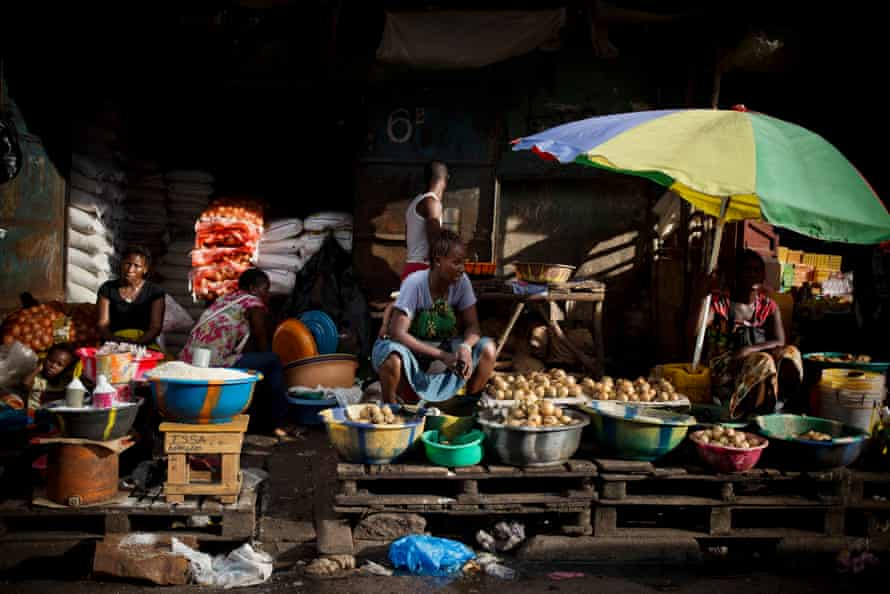 Life returns to the streets of Freetown, Sierra Leone, after the Ebola crisis as fruit and vegetable sellers wait for customers.