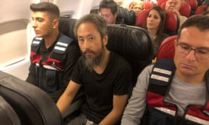 Japanese journalist Jumpei Yasuda sits between two Turkish gendarmes on a flight to Istanbul on Wednesday after his release from captivity.
