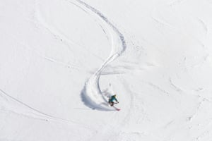 Above view of a freeride skier making a sharp turn in fresh powder snow.2014509