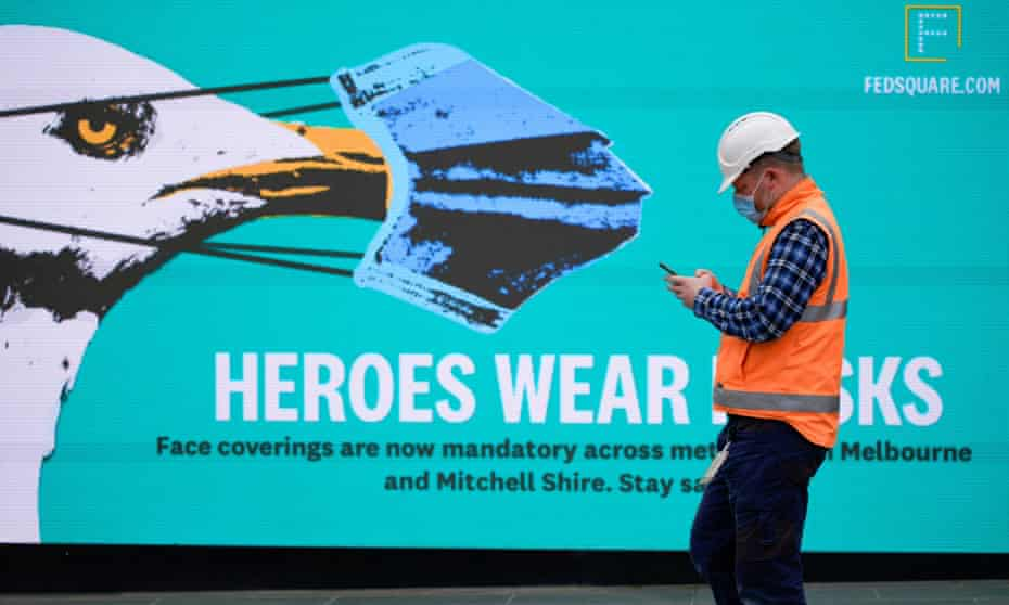 man in hi-viz and mask in front of a heroes wear masks poster