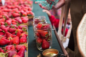 Strawberries are placed into a mason jar she brought after again checking that the plastic punnet would be reused.
