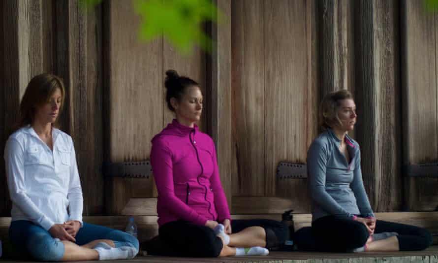 Three women sitting in a row, cross-legged on the ground, meditating