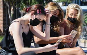Three women wearing face masks use their mobile phones