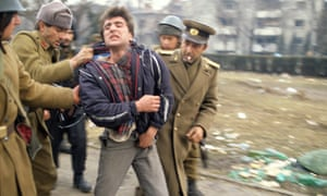 The Romanian revolution of 1989. A collaborator with the Ceaușescu regime is arrested by soldiers.
