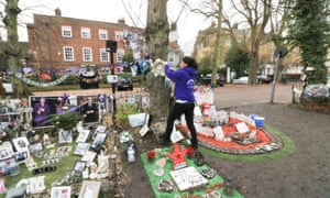 Fans tends to tributes to George Michael at the garden opposite his former home in Highgate.