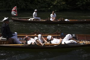 Swan uppers have a nap while being towed upstream on the second day of the annual census on the River Thames