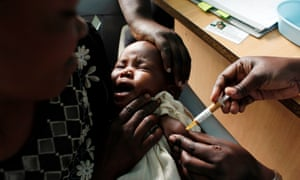 A mother holds her baby as she receives an injection of the Mosquirix malaria vaccine as part of a trial in Kombewa, western Kenya, in 2009.