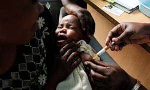 A mother holds her baby as she receives a malaria vaccine in Kombewa, Kenya.