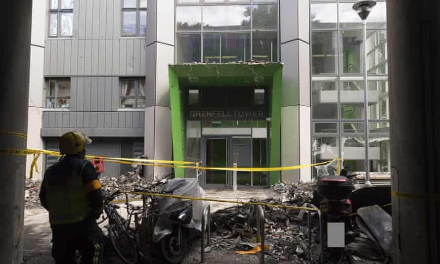 A firefighter stands outside the debris-surrounded entrance to Grenfell Tower after the fire