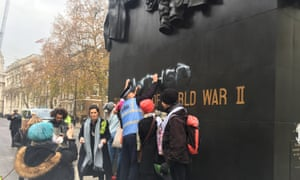 Police and protesters remove graffiti from the memorial to the women of the second world war in Whitehall.