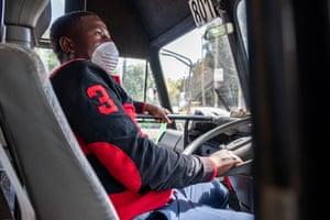 Nicholas Peter sits at the steering wheel of the matatu he drives in Nairobi