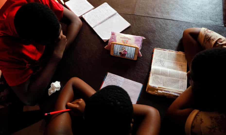 Teenagers watch a live broadcast of church service from home after religious gatherings were suspended during the pandemic, in Accra, Ghana, in March 2020