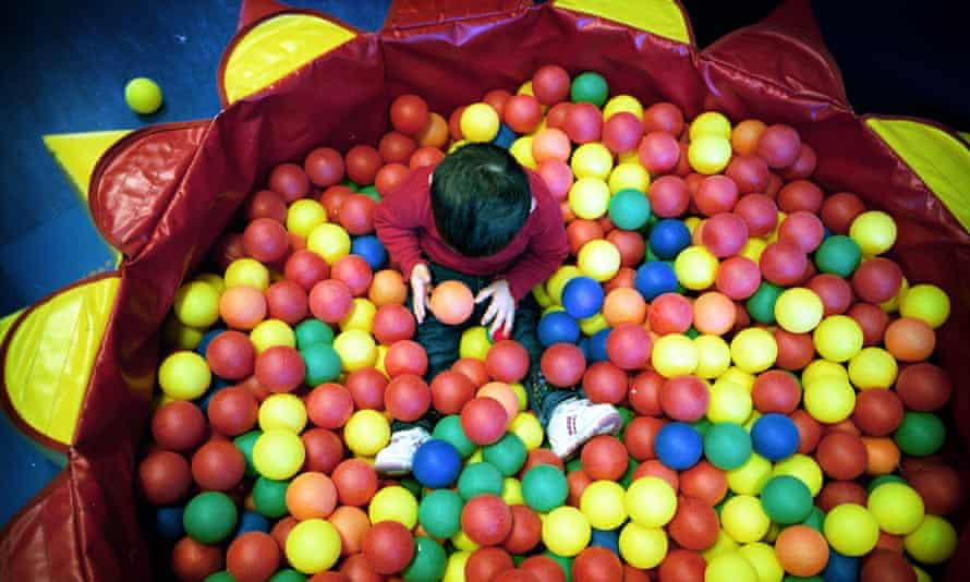 A child playing in a ball pool at a Sure Start centre in north London
