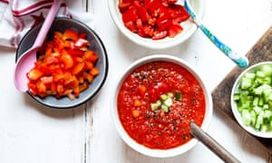 A bowl of gazpacho with cucumber and red pepper topping