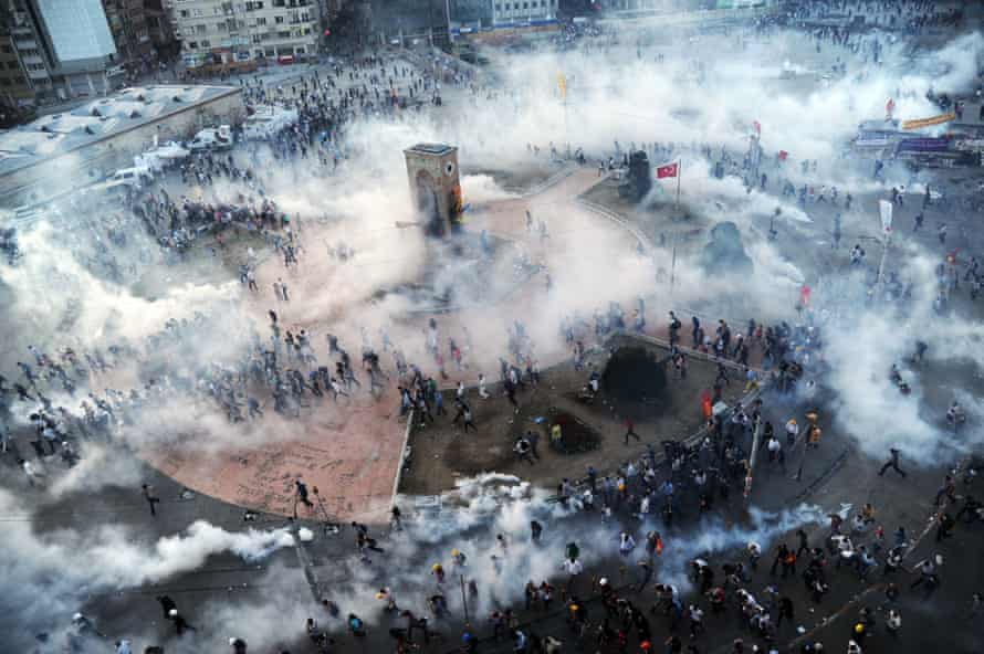 People run as Turkish riot policemen fire tear gas on Taksim square on June 11, 2013. Thousands of anti-government demonstrators gathered initially to contest the urban development plan for Istanbul's Taksim Gezi Park.