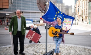 "Activist and musician Madeleina Kay, also known as ""EU Supergirl"" holds a flag and placard as she stands outside the EU Council headquarters on April 10, 2019 in Brussels, Belgium"