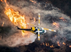 A Los Angeles fire service helicopter flies over the Skirball fire in Bel Air