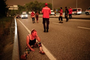 A woman sits on a street during a forest fire in Pedrogao Grande, Leiria District