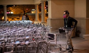 Instacart employee Eric Cohn, 34, picks out a cart outside a Fry's grocery store while wearing a respirator mask to help protect himself from the coronavirus in Tucson, Arizona.