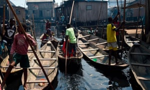 People row boats in a makeshift home in the Makoko riverine slum settlement in Lagos, Nigeria
