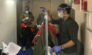 Guardian Angels, a group of medical personnel with the 129th Rescue Wing of the California Air National Guard, working alongside individuals from the Centers for Disease Control and Prevention, don protective equipment after delivering virus testing kits to the Grand Princess cruise ship off the coast of California.